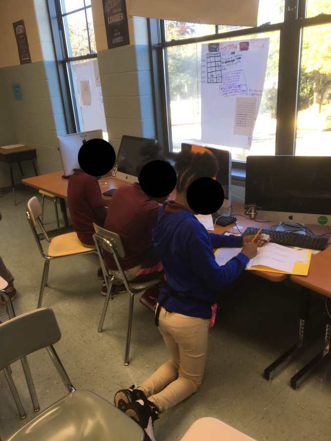 Students working in small groups on gallery walk. This group includes one low SPED, one low gen ed, and one high gen ed student.